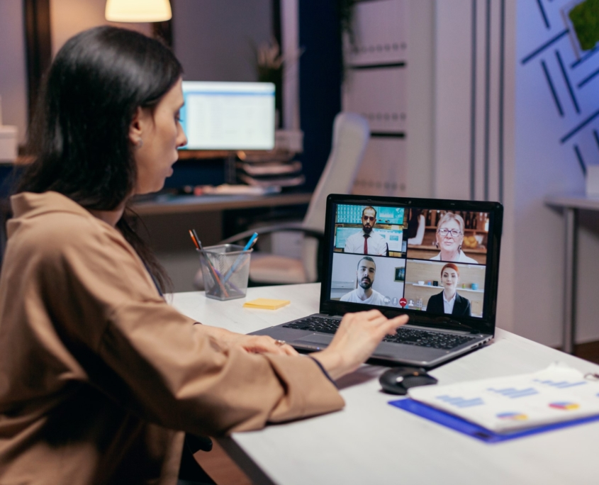 Businesswoman leading a video conference call late night