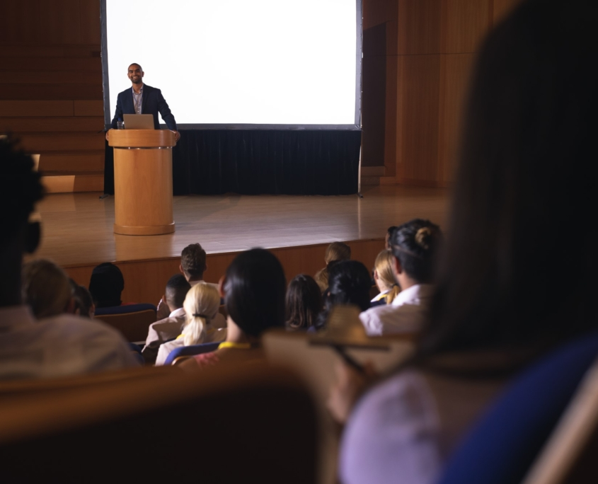 Businessman giving speech in front of audience in the auditorium